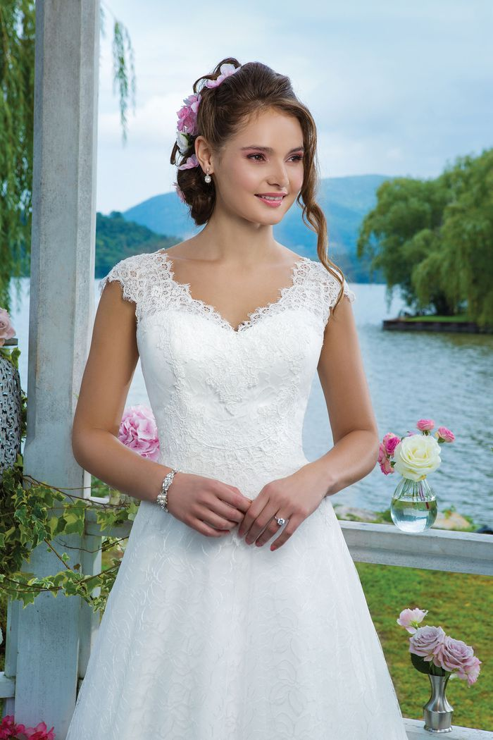 Sweetheart Gowns Style 6095 Alencon lace, embroidered lace and tulle A-line embellished with a v-neck neckline.